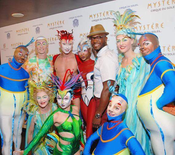 Taye Diggs with colorful characters from Mystère by Cirque du Soleil at Treasure Island Las Vegas