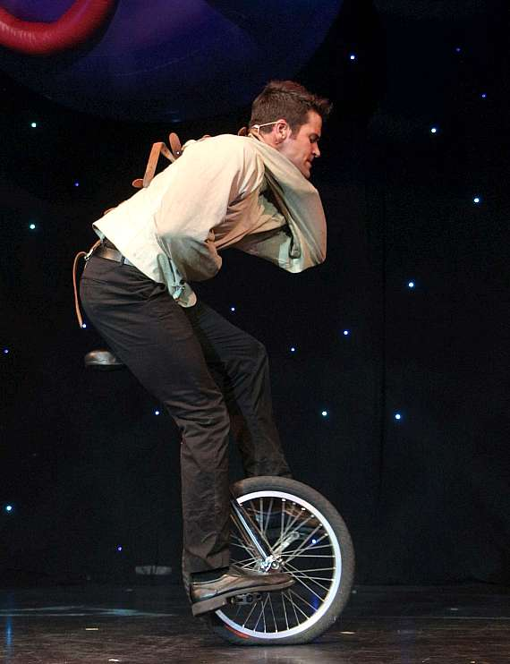 Jeff Civillico escapes from the straightjacket while riding a unicycle