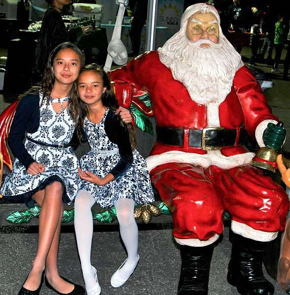 "Keena and Kayla sit with ""Santa"" at Glittering Lights in Las Vegas Motor Speedway"