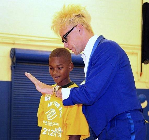 Murray SawChuck performs magic as his volunteer watches very closely