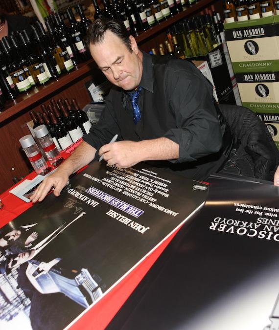 "Dan Aykroyd signs a ""Blues Brothers"" poster"