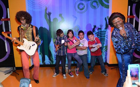 Children pose withwax figures of Jimi Hendrix and James Brown at Madame Tussauds Las Vegas