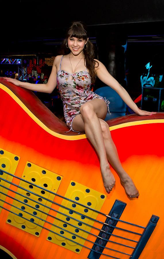 Claire Sinclair sits on KISS member Tommy Thayer's Gibson Les Paul Sunburst guitar at KISS Monster Mini Golf in Las Vegas