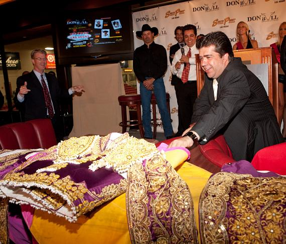 "Pedro Haces Barba, President of Don Bull Productions, shows the press a traditional suit worn by the bullfighters called ""traje de luces"", meaning the ""suit of lights""."