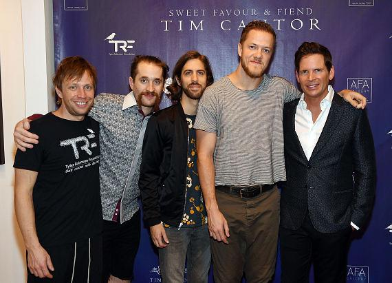 Bass guitarist Ben McKee, drummer Daniel Platzman, guitarist Daniel Wayne and singer Dan Reynolds of Imagine Dragons pose for a photo with artist Tim Cantor at Tim Cantor's Las Vegas art exhibit at AFA Gallery at the Fashion Show Mall