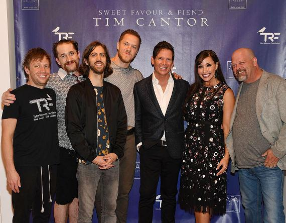Bass guitarist Ben McKee, drummer Daniel Platzman, guitarist Daniel Wayne and singer Dan Reynolds of Imagine Dragons pose for a photo with artist Tim Cantor, Amy Cantor and Rick Harrison at Tim Cantor's Las Vegas art exhibit at AFA Gallery at the Fashion Show Mall