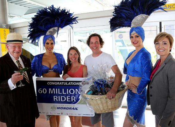 Oscar Goodman, 60 millionth rider Steve Riley and wife Laura Riley, Las Vegas Monorail Company VP and CMO Ingrid Reisman and showgirls