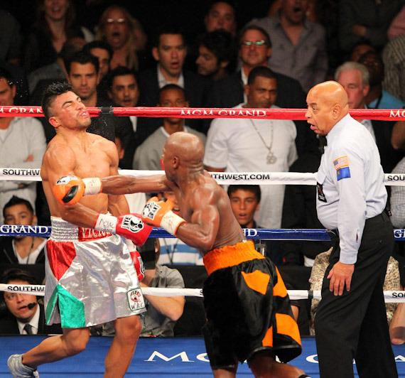 While referee Cortez is communicating with the timekeeper, Mayweather knocks out Ortiz