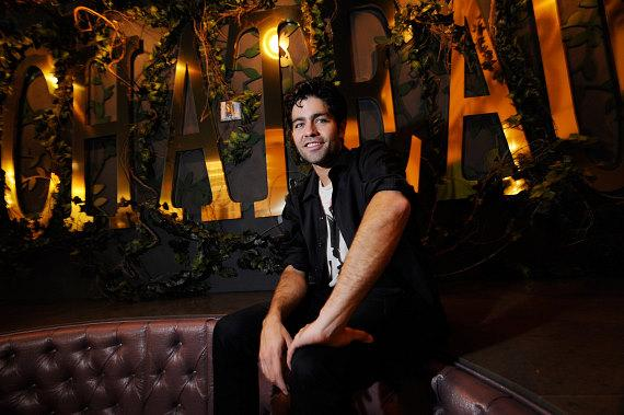 Adrian Grenier sits at Chateau Gardens