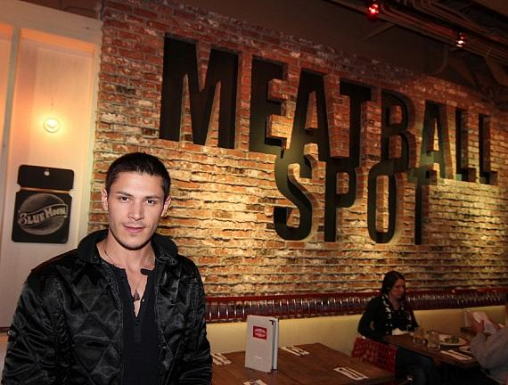 Alex Meraz poses in front of Meatball Spot sign