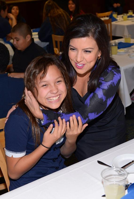 Fox 5 anchor Olivia Fierro hugs a student