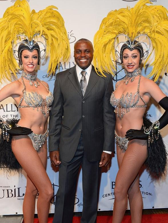 Showgirl Brittany Guinane, former Olympian Carl Lewis and showgirl Taryn Olivieri arrive at the 'Jubilee!' show's grand reopening at Ballys Las Vegas on March 29, 2014 in Las Vegas