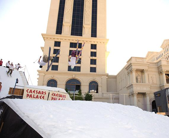 Professional snowboarders and skiers perform tricks on a snow-covered, four-story ski jump at Caesars Palace
