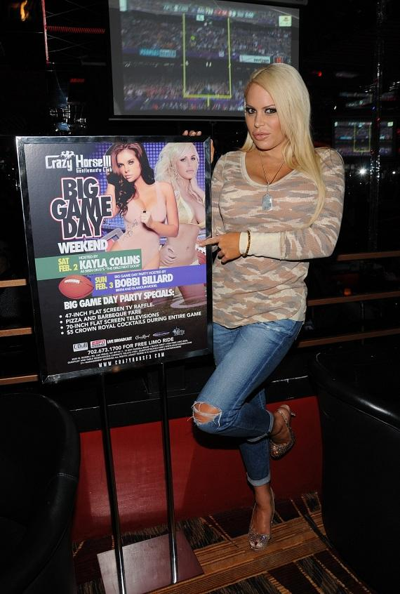 Bobbi Billard poses with 'Big Game' event poster at Crazy Horse III