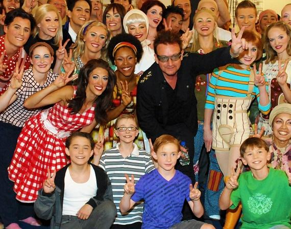 Bono poses with cast members of The Beatles LOVE by Cirque du Soleil