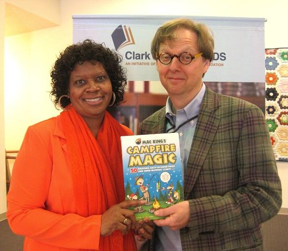 Mac King, pictured with Dr. Beverly Mathis, Principal of Kermit R. Booker Sr. Empowerment Elementary School, donates an autographed copy of his book, Campfire Magic, to the school library during Nevada Reading Week