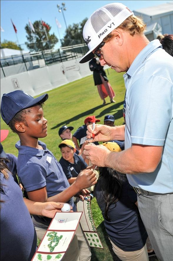 Charley Hoffman autographs golf ball for student