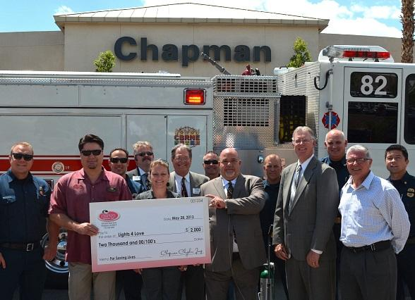 Henderson Fire Department, General Manager of Chapman Chrysler Jeep Ram Gary Brewer, Henderson Mayor Andy Hafen, Lights 4 Love founder James Bryant and Chapman employees stand in front of a fire truck at Chapman Chrysler Jeep Ram during a check presentation on Tuesday, May 28.