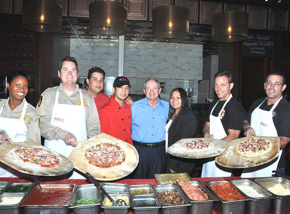Friends of Las Vegas Metro Police Foundation displaying their Five-0 Meatza Pizza and Southern Nevada Burn Foundation showcasing their Parmesan Red Hot pizza with Dom DeMarco's Partner Albert Scalleat and staff members. Each pizza will be featured on the Dom DeMarco's menu throughout October which is National Pizza Month. A portion of the sales of each pizza will go directly to each non-profit.