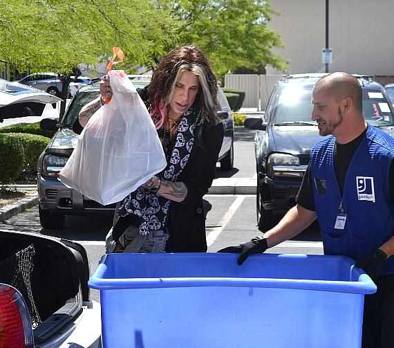 """Steven Tyler"" Tribute Artist Chris VanDahl of Legends in Concert accepts a donation at Goodwill in Las Vegas"