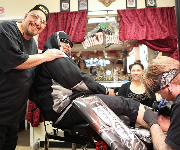 Riviera Hotel & Casino Headliner Pat DiNizio of the Smithereens with Matua J. as he gets a tattoo of DiNizio's face on his lower leg at the 3 Lions Tattoo Shop.