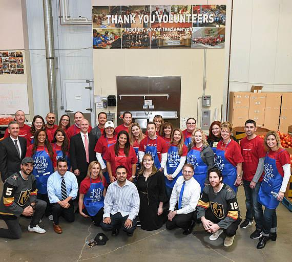 Vegas Golden Knights' Deryk Engelland and James Neal with Bank of America Las Vegas Market President and employee volunteers at Three Square Food Bank