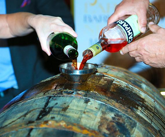 Guests begin to pour Campari and Cinzano 1757 into the 53-gallon Wild Turkey barrel.