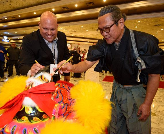 Jason Shkorupa and Chef Masaharu Morimoto paint the lions eyes for good luck