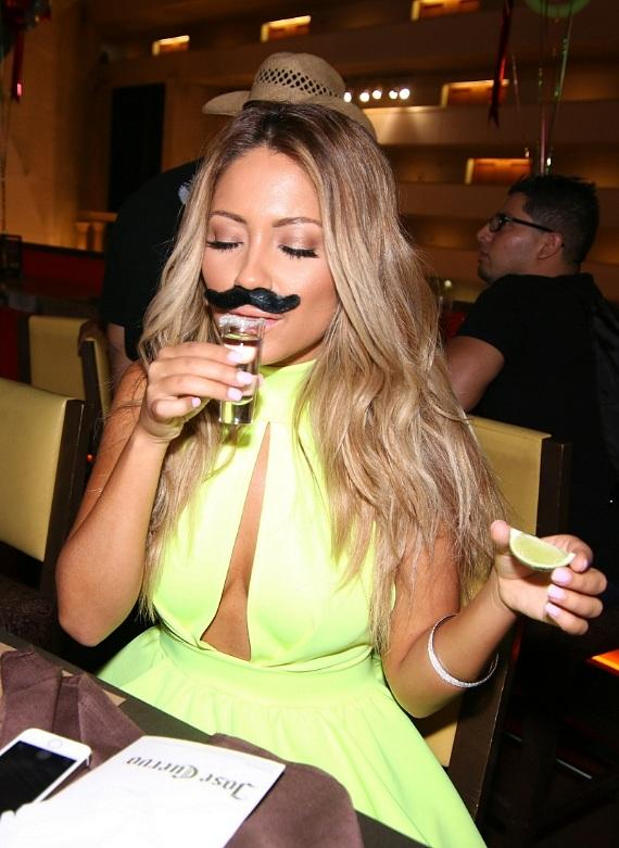 Jessica Burciaga taking a shot of Don Julio tequila with Cinco de Mayo mustache