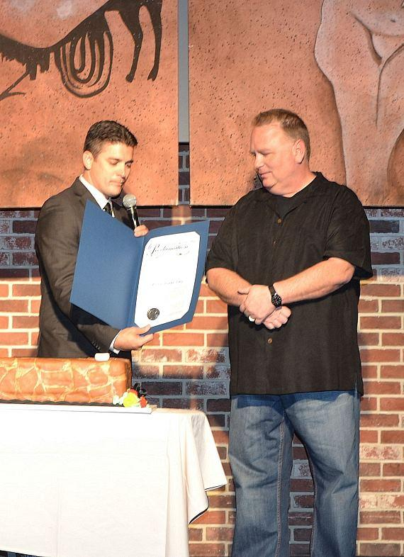"Damian Costa, regional director of entertainment operations at Caesars Entertainment, presents Kevin Burke with a proclamation, signed by Mayor Carolyn G. Goodman naming Monday, May 13, 2013 as ""Kevin Burke Day"" in Las Vegas in recognition of his work as Defending the Caveman's leading caveman for 10 years."