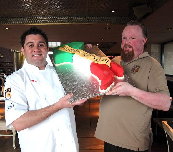 "Executive Chef Geno Bernardo of Nove Italiano and Mixologist Jack ""Sugar"" O'Brien receive a birthday cake in the shape of Italy at the April 9 cooking class"