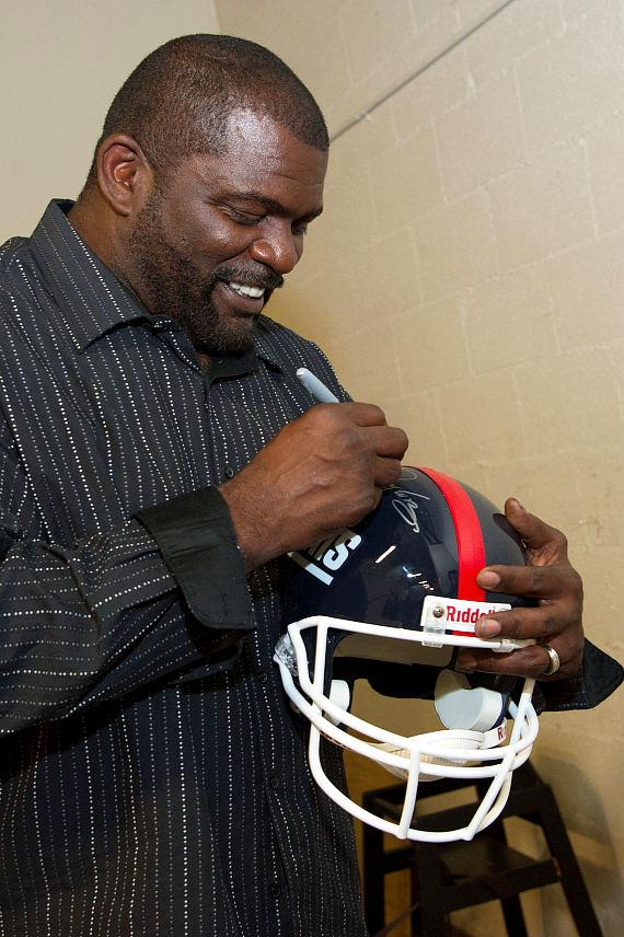 Lawrence Taylor signs a helmet at TAO Las Vegas