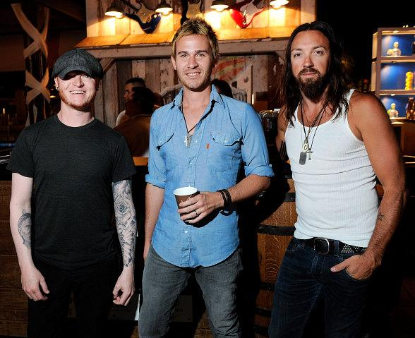 Lifehouse band members Ben Carey, Jason Wade and Rick Woolstenhulme, Jr. pose in front of the guitars at the Lynyrd Skynyrd BBQ + Beer booth