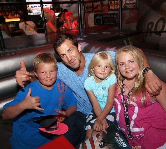 Luke Rockhold takes a photo with young fans