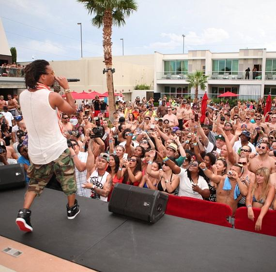 Lupe Fiasco dances on stage while eager fans look on at Palms Pool.