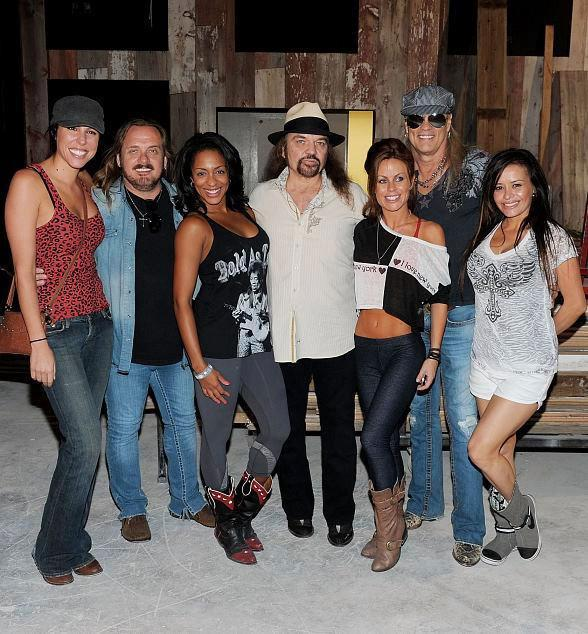Lynyrd Skynyrd band members pose with dancing bartenders at Lynyrd Skynyrd BBQ & Beer at Excalibur Hotel & Casino in Las Vegas