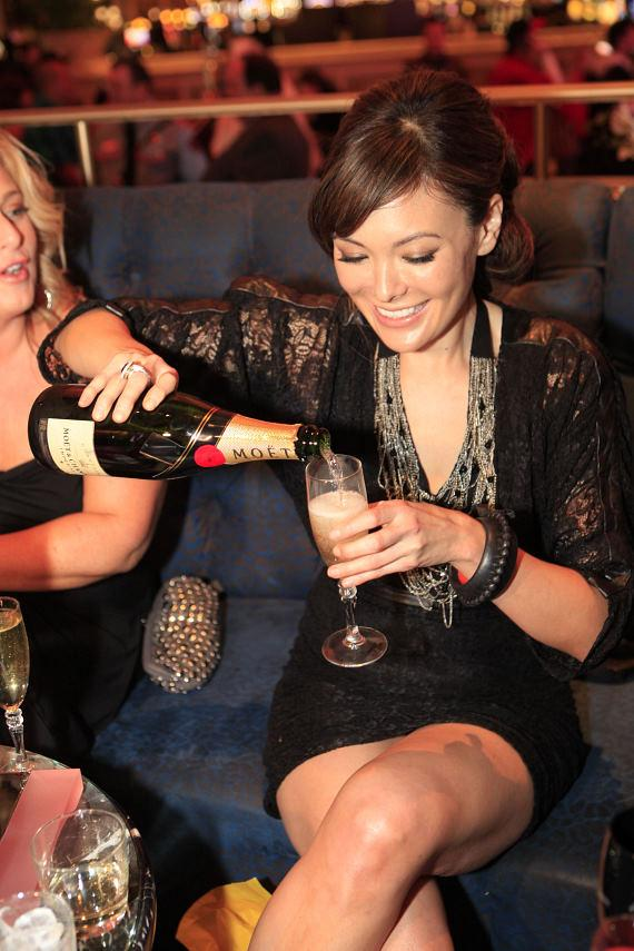 Lindsay pouring a glass of Moet for her friend