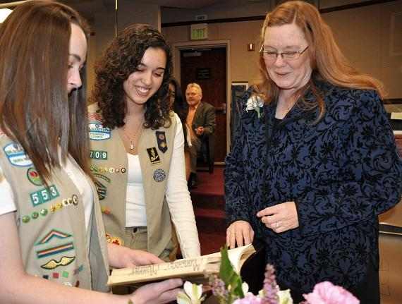 Delaney Mott, Victoria Garcia and Maggie Carlton – District No. 14. Maggie shows the girls her Girl Scout book during her time in the program.