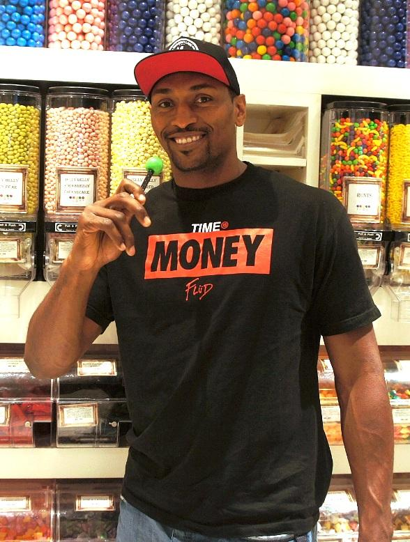 Metta World Peace with a green apple Couture Pop inside Sugar Factory