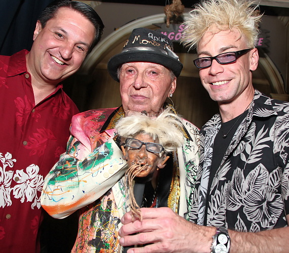 """Magician Douglas """"Lefty"""" Leferovich and comedian Monte Rock III pose with guests at his shrunken head reveal"""