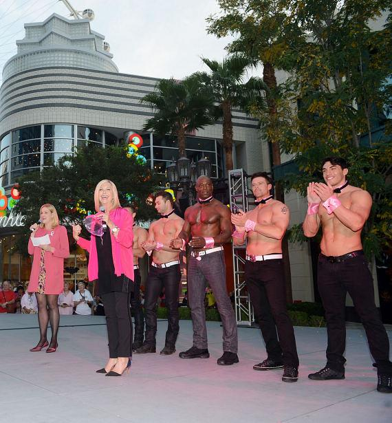 Olivia Newton-John is joined on stage by Flamingo Las Vegas Regional President Eileen Moore, as well as Chippendales from Rio All-Suite Hotel & Casino, at The LINQ Promenade in Las Vegas on Monday, Oct. 6