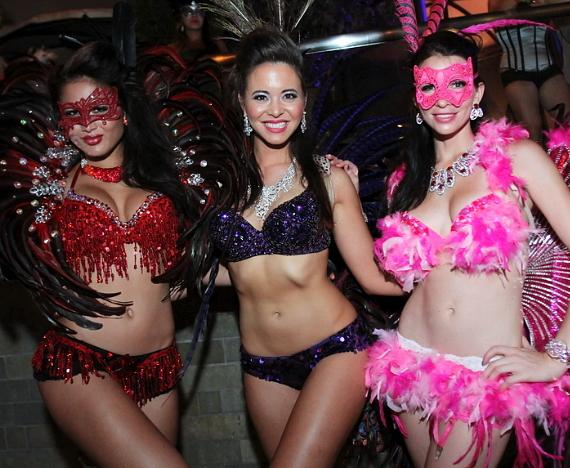 Reveling guests show off their sequined and feathered Midsummer costumes at Palms Pool