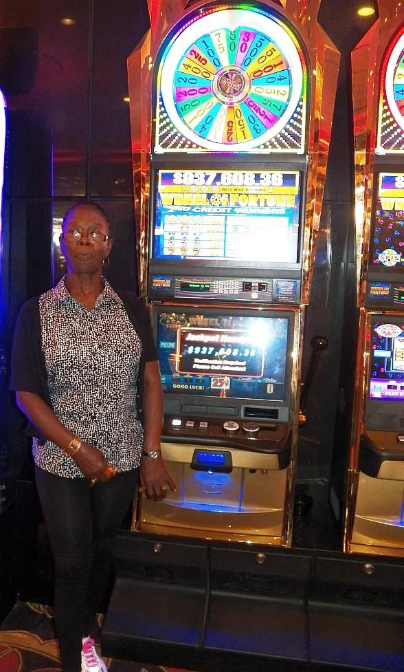 Mozelle Wallace poses with the Wheel of Fortune Slot Machine