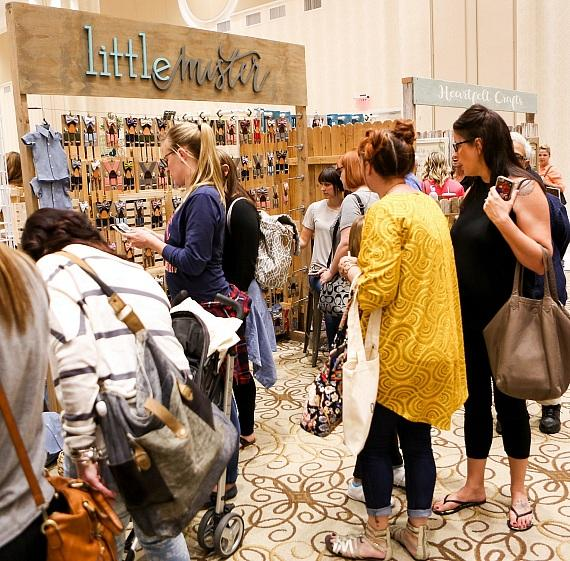 Shoppers peruse items at the Little Mister Booth at Queen Bee Market