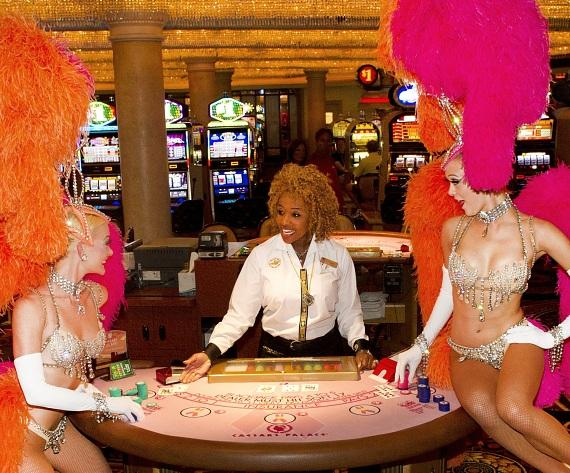 "Showgirls from Bally's hit show ""Jubilee!"" play a hand at a signature pink table at Caesars Palace in honor of Breast Cancer Awareness mo"