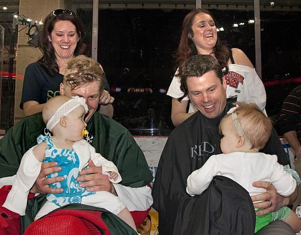Wranglers left wing Robbie Smith (left) and Mougenel get their heads shaved while their daughters look on