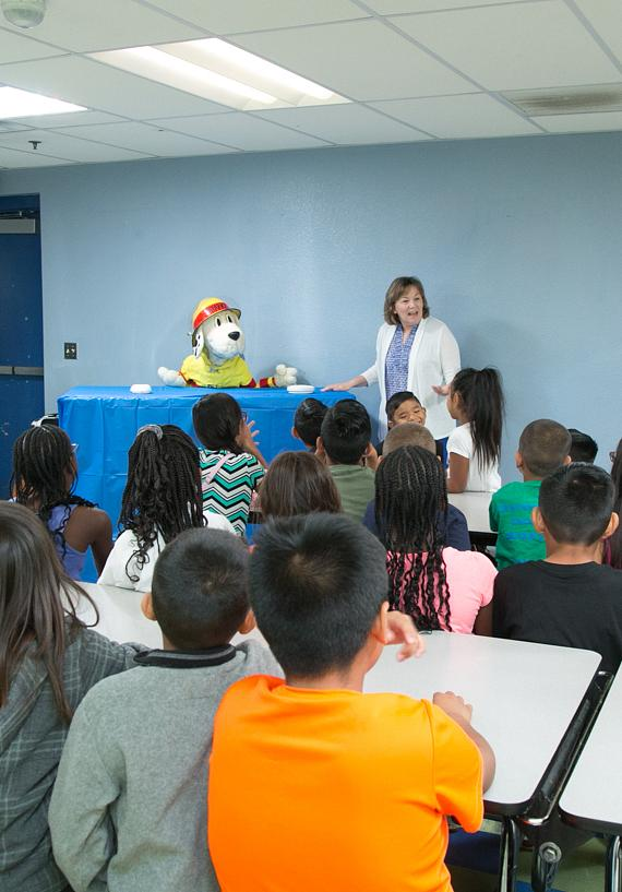 Sparky The Fire Dog and Judy Comoletti, NFPA's division manager of public education give smoke alarm tips to the children of James Clubhouse of Boys & Girls Clubs of Las Vegas