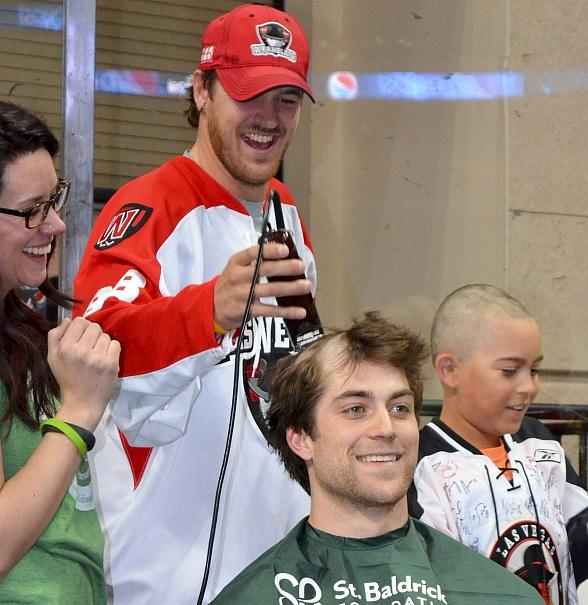 Wranglers' forward Justin Bernhardt (left) helped shave the head of teammate John Armstrong (right) during the team's annual on-ice fundraiser for St. Baldrick's Foundation