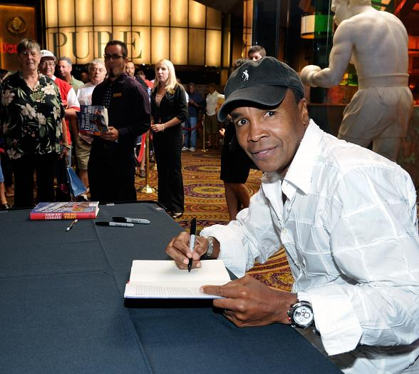 Hall of Famer Sugar Ray Leonard autographs a copy of his book as onlookers gather to get a glimpse of the legendary boxer