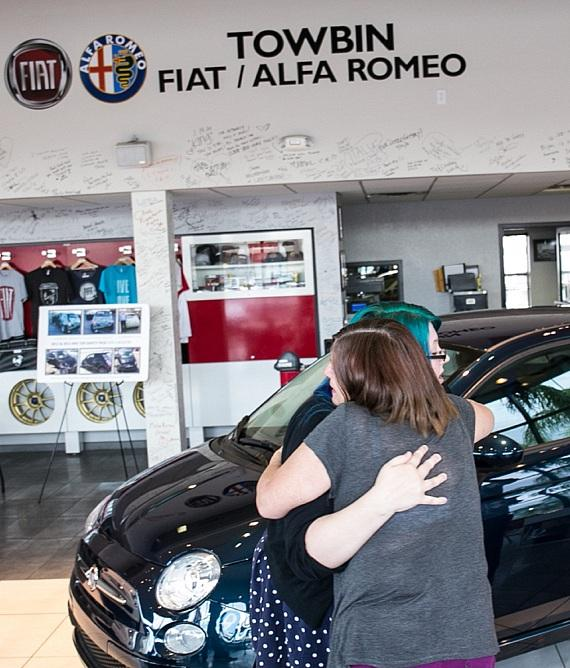 Family embrace in front of beloved FIAT